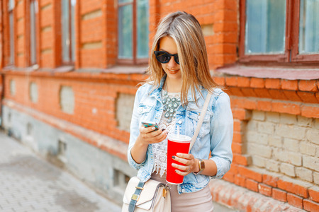 Beautiful woman in a denim jacket holding a red cup and writes a message on the phone on the background of a brick building. Stock Photo