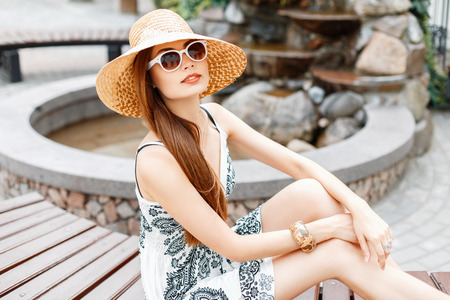 Young beautiful girl in sunglasses and straw hat sitting near the fountain in the park.