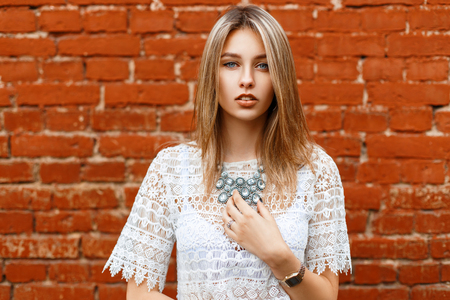 Beautiful girl in white vintage lace blouse with jewelry on a background of bricks Stock Photo