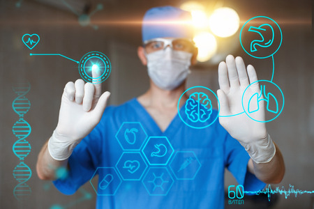Doctor in blue uniform touch display with infographics. Modern professional surgeon in the operating room. Medical icons on the desktop.