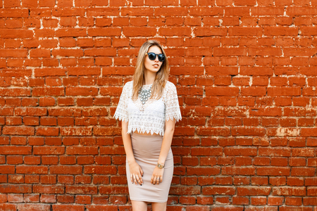 Beautiful stylish modern woman in white lace vintage blouse and skirt posing near red brick wall