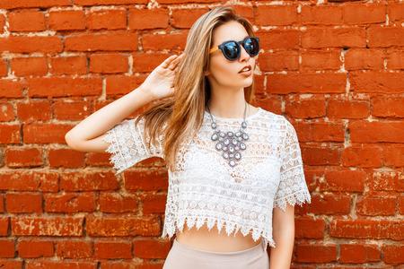 Cheerful young beautiful woman in sunglasses posing near brick wall Stockfoto