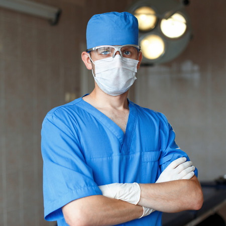 Surgeon in blue uniform, glasses and hat stands in the operating room on the background of bright lights