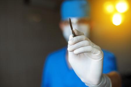 cirujano: El doctor plástico con un bisturí en la mano comienza a funcionar. Profesional médico cirujano en el quirófano