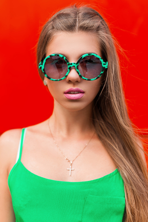 green clothes: Trendy colorful portrait of pretty woman in a modern green sunglasses with pink lips and green clothes on a bright red background. Stock Photo