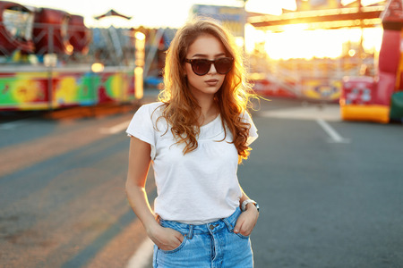 Stylish beautiful girl in sunglasses at sunset background