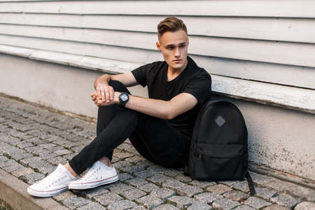 Model man in black clothes with bag sits near wall
