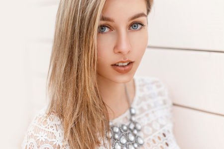 Portrait of a beautiful blond girl with blue eyes on the background of a wooden wall.