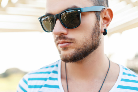 blue stripe: Close-up portrait of a young handsome man in sunglasses on a sunny day. Stock Photo