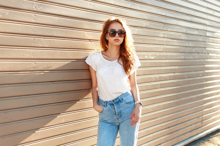 Beautiful stylish girl in a vintage blue jeans and white T-shirt standing near a wooden wall.