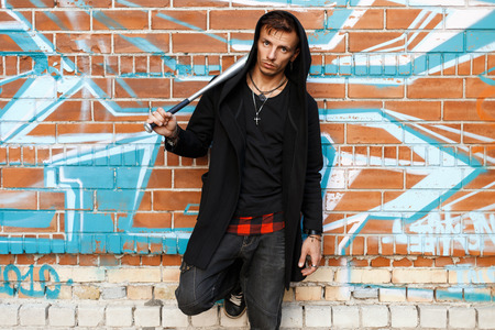 street creed: Stylish handsome man with a bat is posing near brick wall with graffiti.