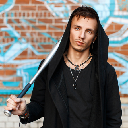 street creed: Handsome man with a bat in black clothes in the hood near the brick wall with graffiti