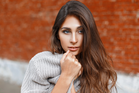 cable knit: Beautiful woman in a gray sweater hiding Stock Photo
