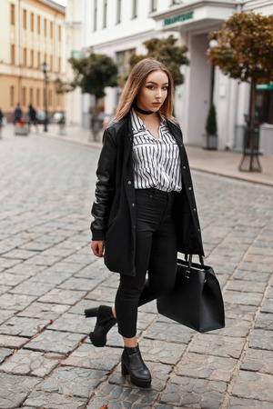 Beautiful young girl model in a fashionable coat with a bag walks in the city