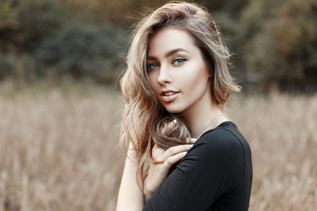 Portrait of a young woman in a black shirt on a background of nature