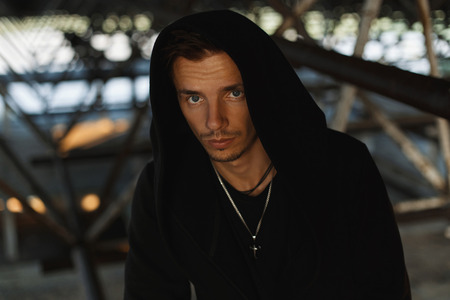 Handsome young man in a black robe with a hood.