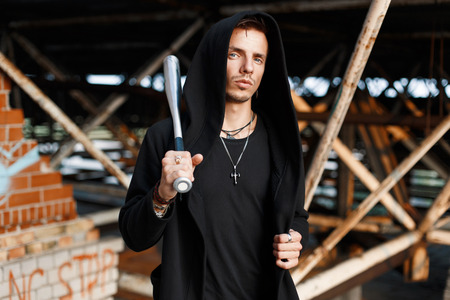 Trendy man with a hood holds a bat on the background of the old buildings Stock Photo