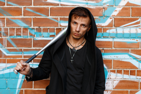 street creed: Angry guy near brick wall with graffiti holding a metal bat