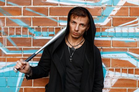 street creed: Angry guy near brick wall with graffiti holding a metal bat