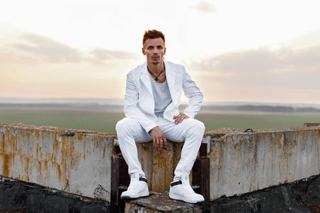 지붕에 앉아 세련 된 흰색 옷에 젊은 잘 생긴 남자.