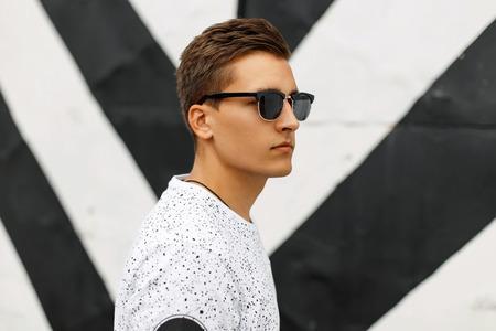 Jonge knappe man met een kapsel en zonnebril op een achtergrond van zwarte en witte strepen.