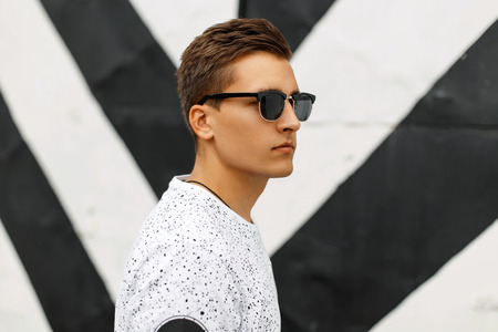 strip shirt: Young handsome guy with a hairstyle and sunglasses on a background of black and white stripes. Stock Photo