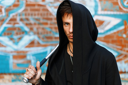 street creed: Stylish handsome man in black clothes with a hood standing near a brick wall with graffiti. Man holding bat.