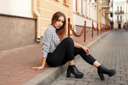 strip shirt: Pretty hot woman sitting on the curb. Stock Photo