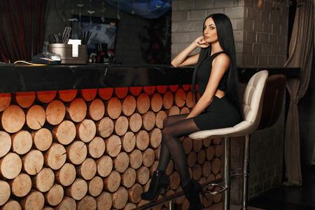 エレガントなドレスの美しい少女は、バーで椅子に座っています。 写真素材 - 67607516