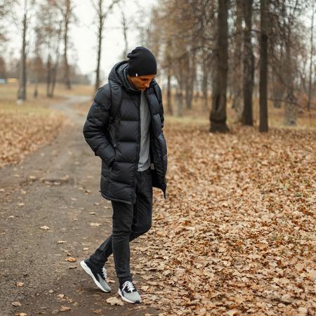Knappe jonge man in een zwarte winter jas en gebreide muts in het park. Stockfoto