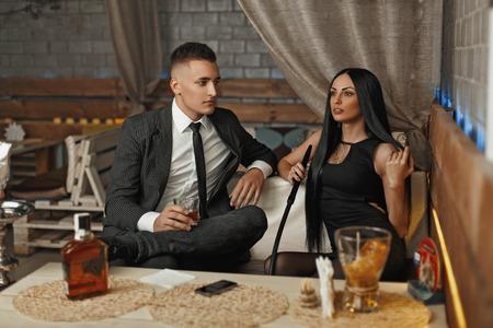Jonge mooie paar ontspannen aan de bar. De man drinkt whisky. Vrouw rookt een hookah