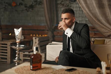 モダンなバーでウィスキーを飲みながらスーツでハンサムな若い男