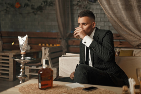 Handsome young man in a suit drinking whiskey in the modern bar