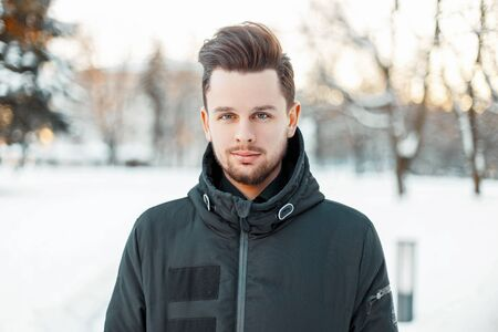 parka: Handsome man with a beard and hairstyle in winter jacket in the park