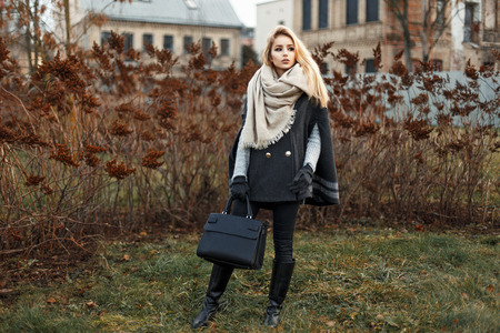 Beautiful young blonde woman in a stylish autumn coat with a black handbag fashion Stockfoto