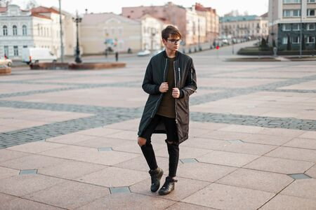 casual men: Stylish guy with glasses in trendy jacket and torn jeans with black sneakers in the city