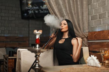 Het mooie meisje rookt een waterpijp en laat de rook. Vrouw die in een bar