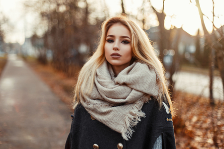 Beautiful young blond girl in coat and scarf on the background of autumn park.