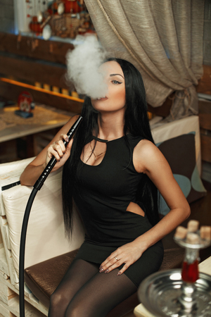 Beautiful girl in stylish black dress smokes a hookah and lets the smoke. Stock Photo