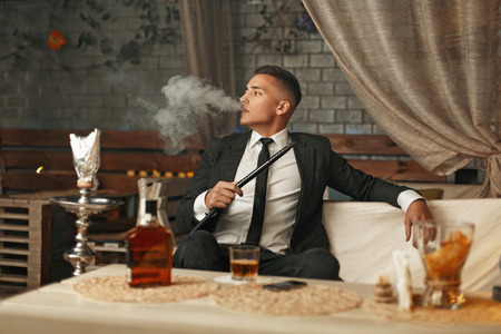 Handsome stylish man in a suit smoking a hookah 스톡 콘텐츠