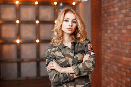 militaire sexy: Stylish young beautiful woman in trendy military jacket on a background of lights