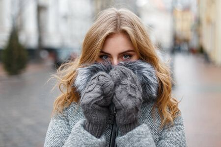 mitt: Beautiful young girl in knitted mittens hides his face and warmed Stock Photo