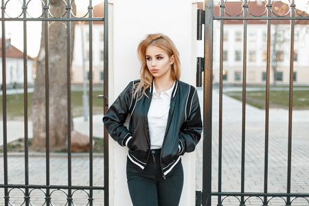 Beautiful young blond woman in a black fashionable jacket and jeans near a fence