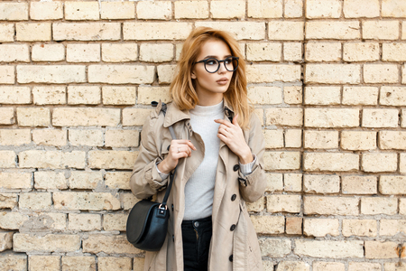 Pretty hipster woman in stylish glasses and trendy coat near the vintage brick wall