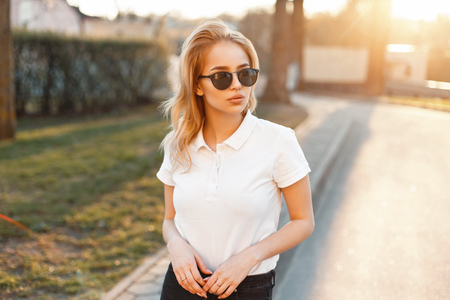 Young girl in trendy sunglasses and white polo shirt in a spring day at sunset Stock Photo