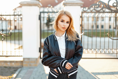 Beautiful blond woman in fashionable black jacket and white polo shirt near the fence on a sunny day