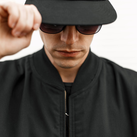 Stylish young man in sunglasses and a black cap