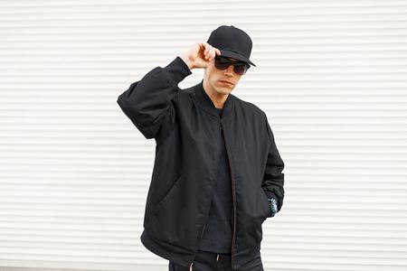 Stijlvolle knappe man in zwarte trendy moderne kleding in de buurt van een witte metalen muur