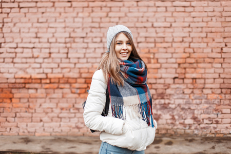 Young woman smiling in a white jacket and bright fashionable scarf near the wall Фото со стока