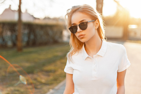 Stylish young cute girl in sunglasses and white polo at sunset